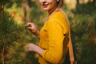 Midsection of smiling woman standing amidst pine trees at forestの写真素材 [FYI03724558]
