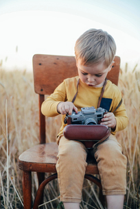 Curious boy adjusting vintage camera while sitting on chair amidst wheat fieldの写真素材 [FYI03724645]
