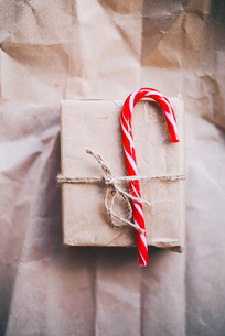 Candy cane tied up with Christmas present on brown paperの写真素材 [FYI03724667]