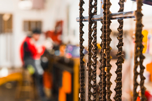 Close-up of metallic chains with man in background at workshopの写真素材 [FYI03724718]