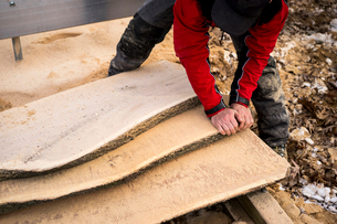 High angle view of male carpenter carrying wooden planks at backyardの写真素材 [FYI03724732]