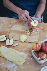 Cropped hands of woman cutting apple for preparing cinnamon bun at homeの写真素材 [FYI03724897]