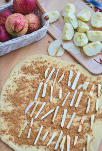 High angle view of apple slices and ground cinnamon layered on pastry dough at kitchenの写真素材 [FYI03724900]