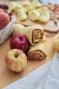 High angle view of apple slices and ground cinnamon rolled in pastry dough on kitchen counterの写真素材 [FYI03724902]