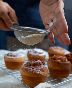 Cropped hands of woman sieving icing sugar on cinnamon bunsの写真素材 [FYI03724904]