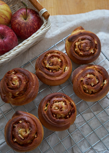High angle view of baked cinnamon buns on metal grate at kitchenの写真素材 [FYI03724905]