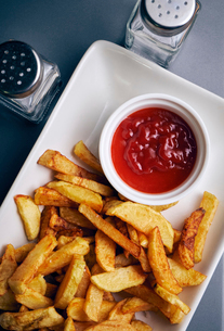 Close-up of french fries and tomato sauce served in plate on tableの写真素材 [FYI03724935]