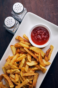 High angle view of french fries and tomato sauce served in plate on tableの写真素材 [FYI03724936]