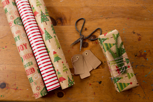 Close-up of scissors by rolled up wrapping papers and Christmas present on tableの写真素材 [FYI03724969]