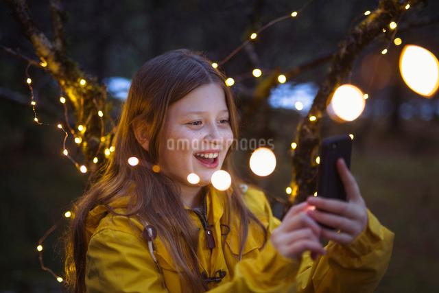 Cheerful girl using smart phone amidst illuminated string lights decoration at nightの写真素材 [FYI03725068]