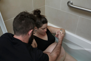 Man comforting pregnant woman lying in bathtub at hospitalの写真素材 [FYI03725384]