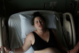 High angle view of painful pregnant woman lying on hospital bedの写真素材 [FYI03725387]