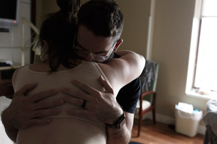 Man embracing pregnant woman in hospital wardの写真素材 [FYI03725390]