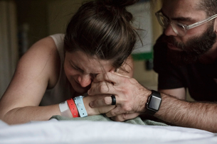 Close-up of man comforting painful pregnant woman on hospital bedの写真素材 [FYI03725397]