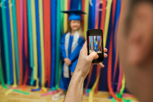 Cropped image of father photographing daughter wearing graduation gown at homeの写真素材 [FYI03725506]