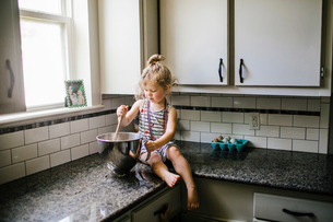 Girl preparing food in container while sitting on kitchen counter at homeの写真素材 [FYI03725551]