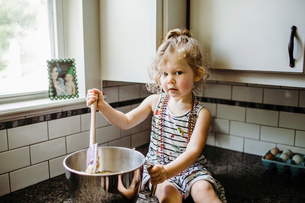 Portrait of cute girl preparing food in container while sitting on kitchen counter at homeの写真素材 [FYI03725552]