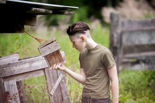 Teenage boy holding birdhouse while standing on fieldの写真素材 [FYI03725714]