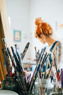 Close-up of paintbrushes with artist in background at studioの写真素材 [FYI03725862]