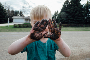 Boy with dirty hands standing on roadの写真素材 [FYI03727442]