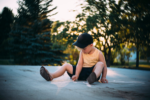 Boy drawing with chalk while sitting on street during sunsetの写真素材 [FYI03727585]