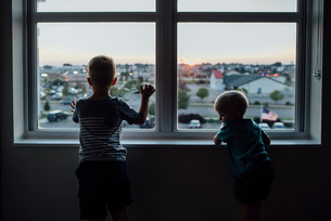 Rear view of brothers looking through window while standing at home during sunsetの写真素材 [FYI03727716]