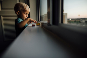 Side view of baby boy playing with toy cars on window sill at homeの写真素材 [FYI03727722]