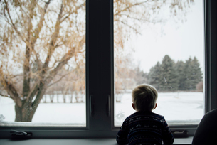 Rear view of baby boy looking through window while standing at homeの写真素材 [FYI03727724]