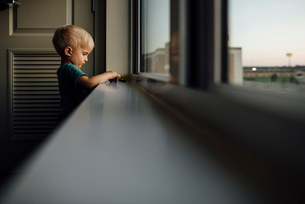 Side view of baby boy playing with toy cars on window sill at home during sunsetの写真素材 [FYI03727726]