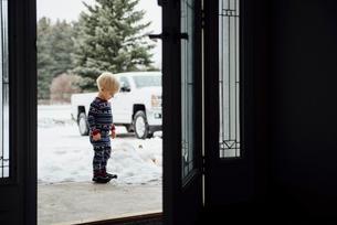 Side view of baby boy standing on snow seen through doorwayの写真素材 [FYI03727727]