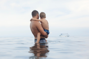 Side view of shirtless father carrying son while standing in sea against cloudy skyの写真素材 [FYI03727747]