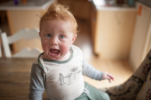 High angle portrait of baby boy with mouth open sitting on table at homeの写真素材 [FYI03727775]