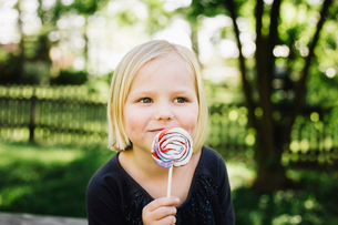 Close-up of girl looking away while eating lollipopの写真素材 [FYI03728124]