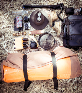 High angle view of camping equipment with personal accessories on fieldの写真素材 [FYI03728131]