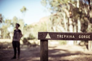 Close-up of information sign with woman standing in background at desertの写真素材 [FYI03728133]