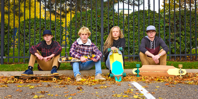 Portrait of friends with skateboards sitting on footpath at park during autumnの写真素材 [FYI03728191]