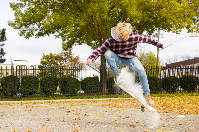 Man with powder paint skateboarding at park during autumnの写真素材 [FYI03728196]