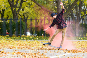 Teenage boy with powder paint skateboarding on footpath at park during autumnの写真素材 [FYI03728197]