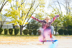 Portrait of man with powder paint jumping while skateboarding at park during autumnの写真素材 [FYI03728203]