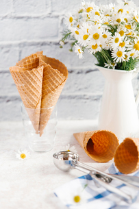 Close-up of ice cream cones with flower vase and serving scoop against wall on tableの写真素材 [FYI03728413]