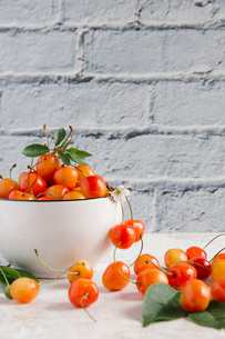 Close-up of cherries on table against wallの写真素材 [FYI03728414]