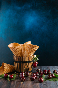 Close-up of ice cream cones with cherries on table against colored backgroundの写真素材 [FYI03728418]