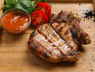 Close-up of grilled meat with sauce on wooden trayの写真素材 [FYI03728424]