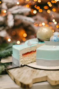 Close-up of cake on cutting board against Christmas Treeの写真素材 [FYI03728427]
