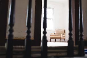 Chair in domestic room seen through metallic railingの写真素材 [FYI03728656]