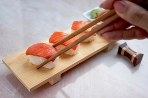 Cropped hand of woman picking sushi with chopsticksの写真素材 [FYI03728664]