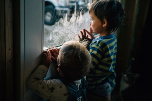 Rear view of siblings looking through window at homeの写真素材 [FYI03728765]