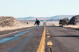 Full length of man skateboarding on road amidst field against clear skyの写真素材 [FYI03728885]