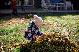 Baby girl playing by heap of leaves on field in yard during autumnの写真素材 [FYI03728936]