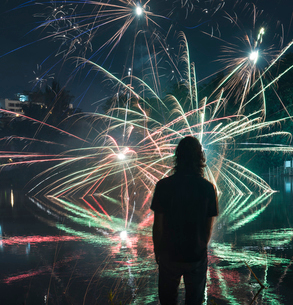 Rear view of man looking at firework display in city at nightの写真素材 [FYI03728987]